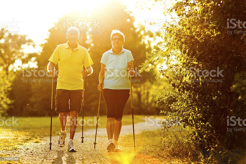 retirees nordic walking sunlight royalty-free stock photo