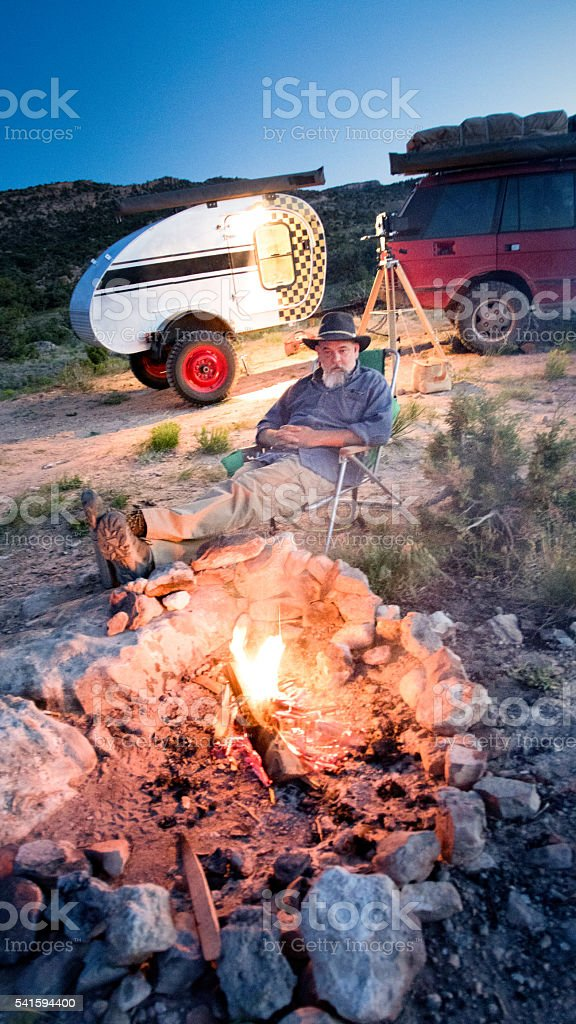 Retirement Aged Caucasian Man Sitting by a Campfire, Camper stock photo