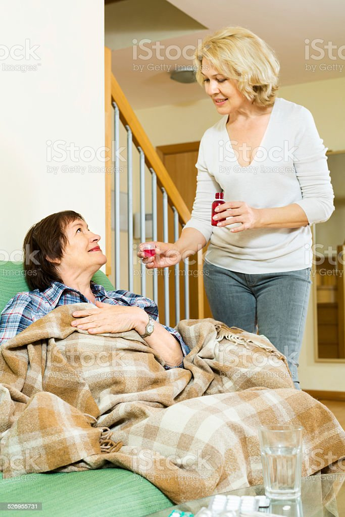 retirement home employee offering  mixture to mature patient stock photo