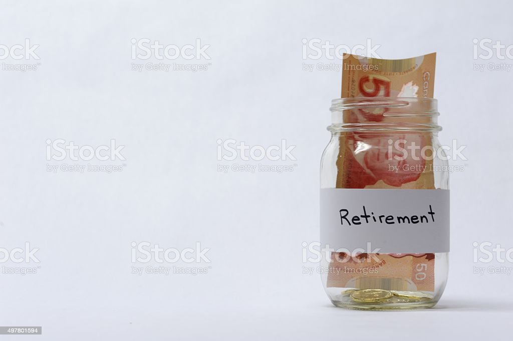 Retirement Savings Jar With Coins And Banknotes stock photo