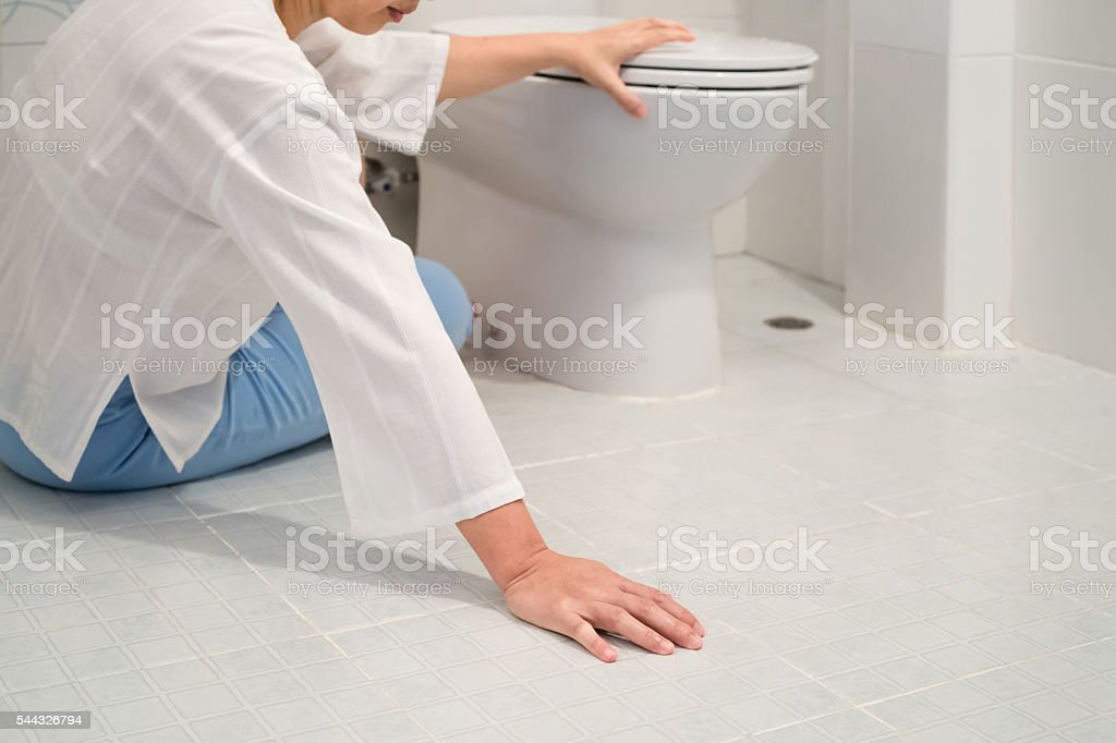 Retirement woman fell down in a restroom stock photo
