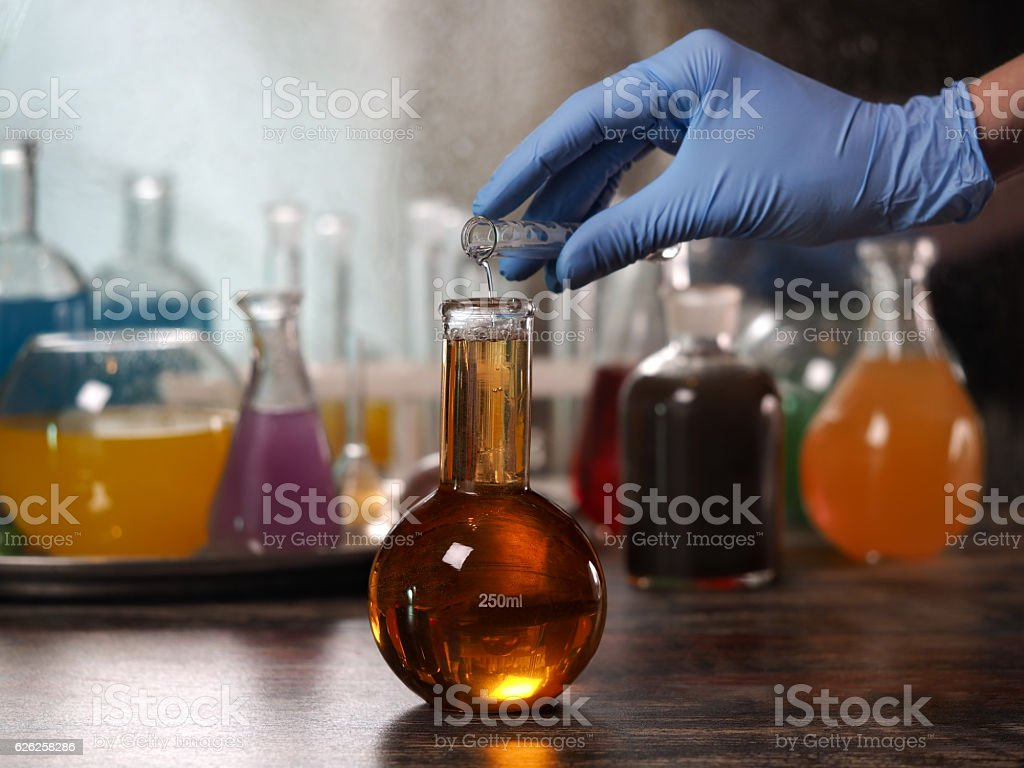 Retort with clear water. Hand in glove tube. stock photo