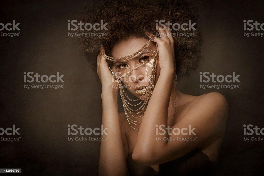 Retrato en estudio de chica afro-asiatica con maquillaje dorado. stock photo