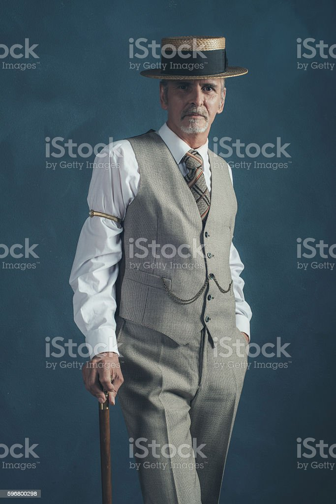 Retro 1920s dandy in suit standing with cane. stock photo