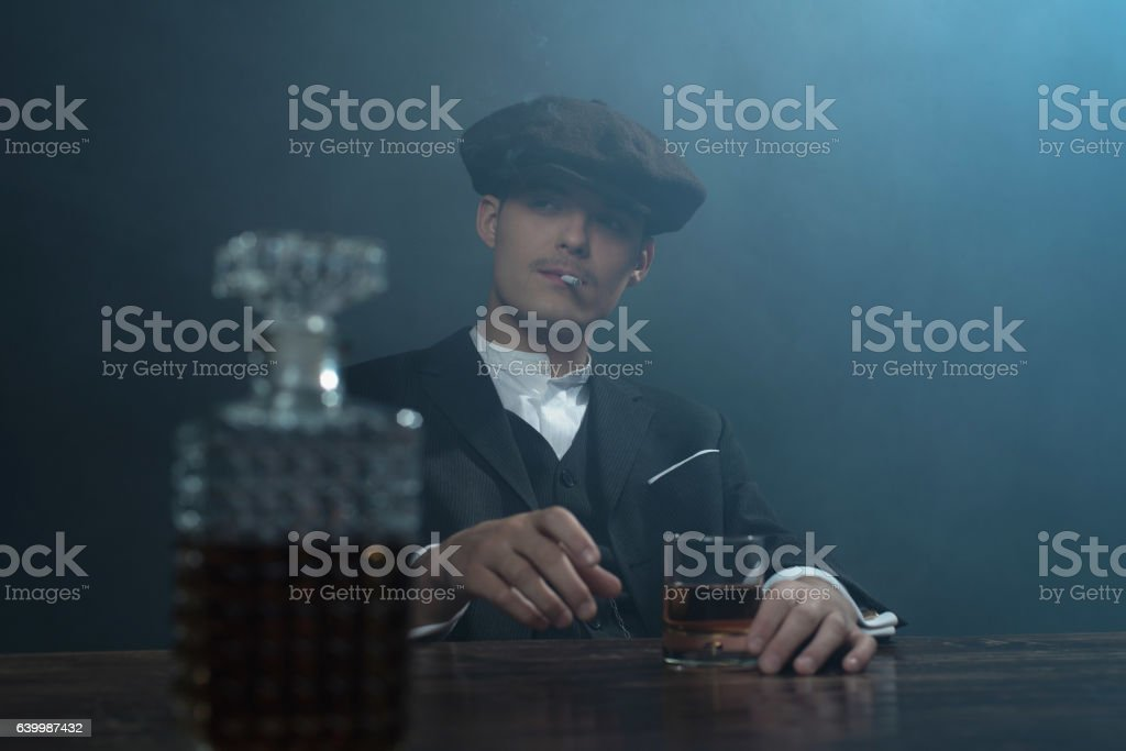 Retro 1920s english gangster sitting at table with whiskey. stock photo
