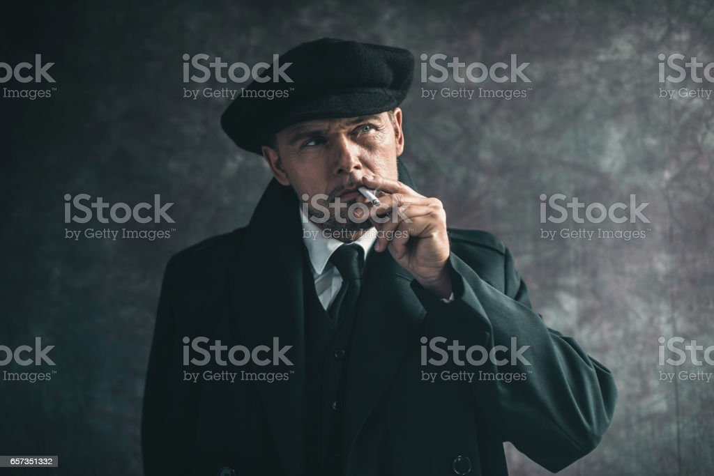 Retro 1920s english gangster smoking cigarette. Wearing black coat and flat cap. stock photo