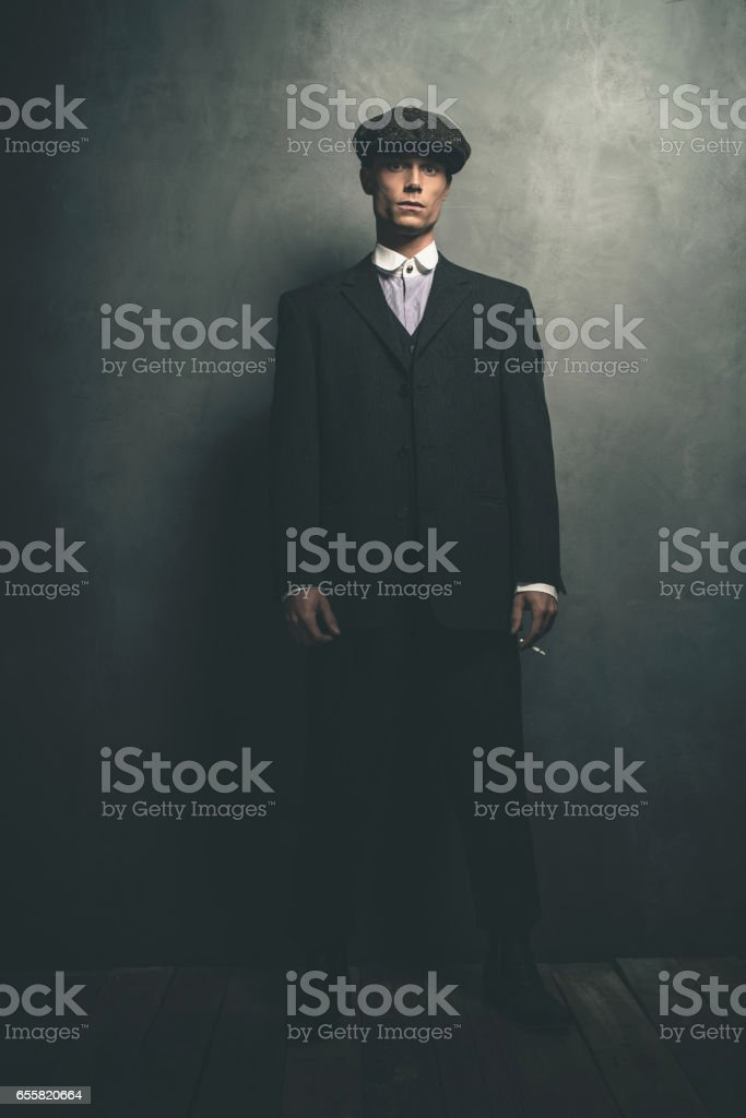 Retro 1920s english gangster standing with cigarette. Wearing suit and flat cap. stock photo