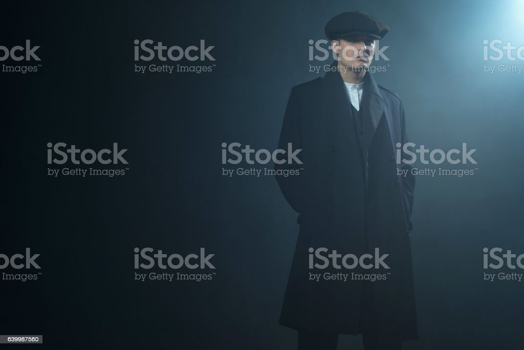 Retro 1920s english gangster wearing coat and flat cap. stock photo