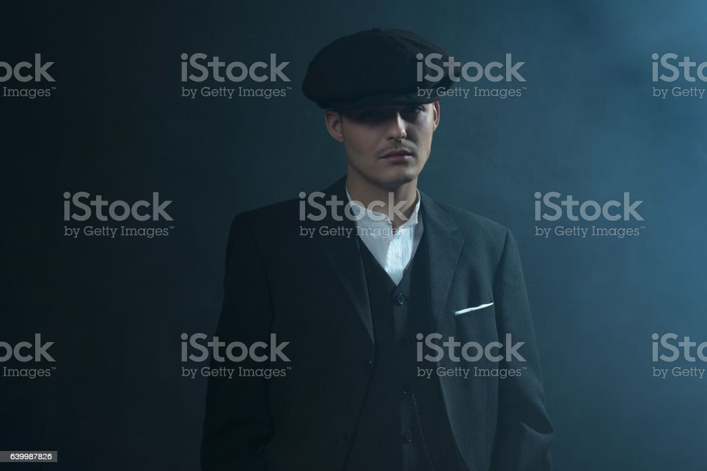 Retro 1920s english gangster wearing suit and flat cap. stock photo