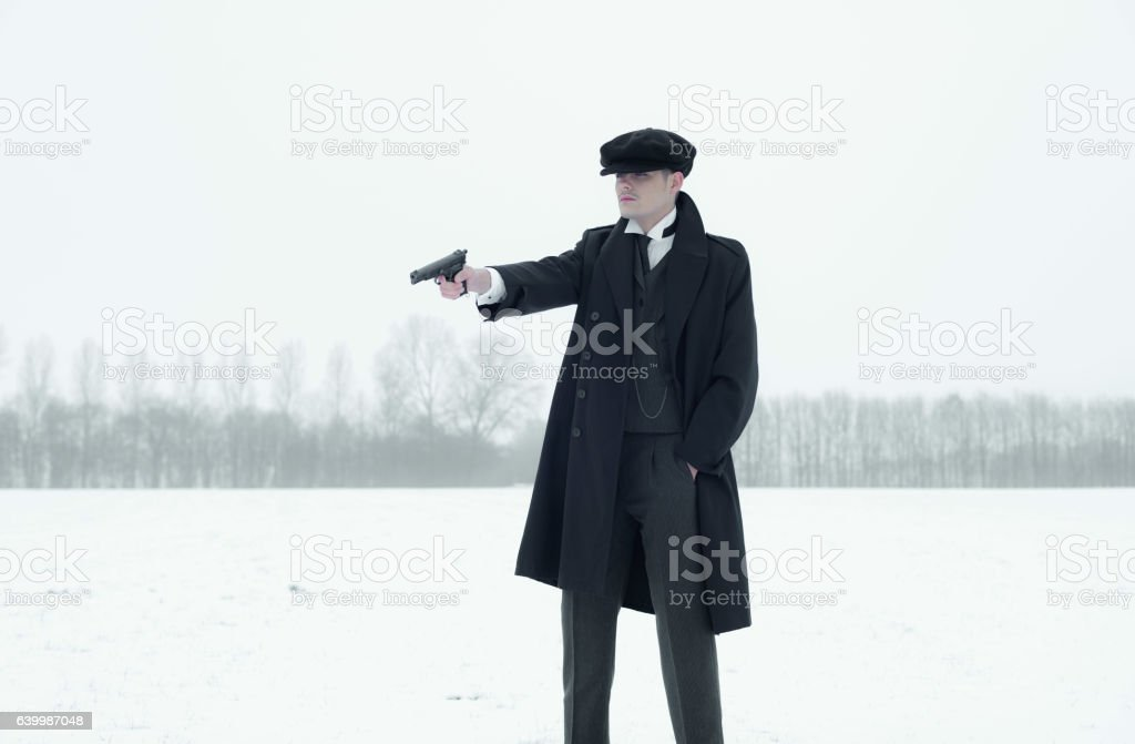 Retro 1920s english gangster with black coat and flat cap. stock photo