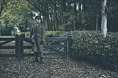 Retro 1940s military officer standing at wooden fence.