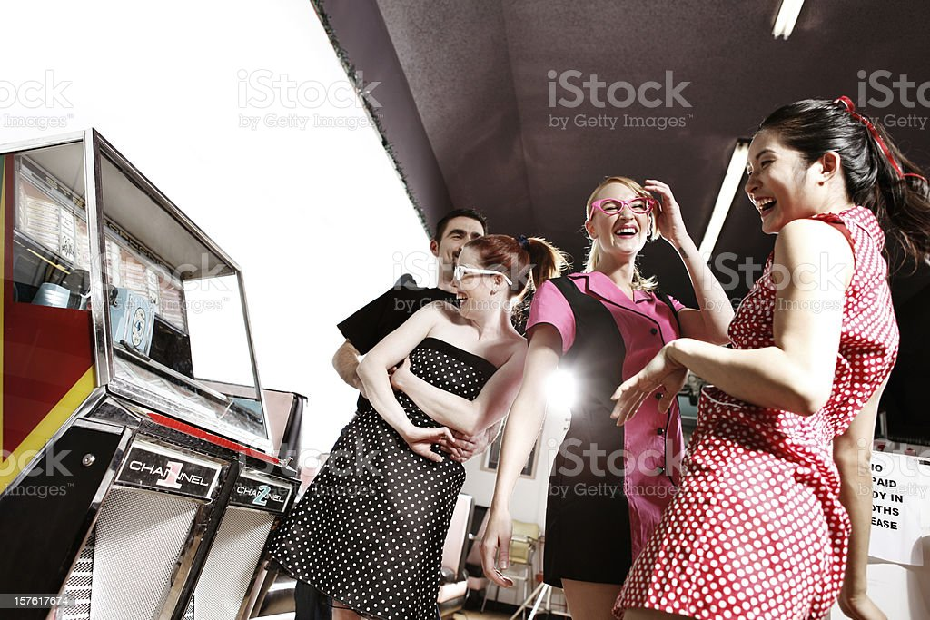 Retro 1950's Friends Dancing by the Jukebox in Soda Shop stock photo