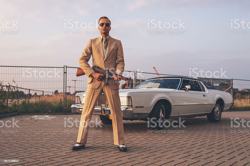Retro 1970s gangster holding gun standing in front of car. stock photo