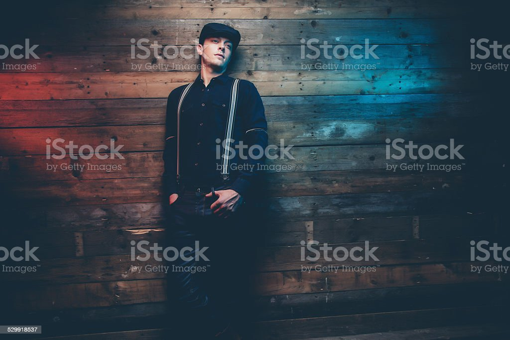 Retro 30s fashion man wearing blue cap, shirt and braces. stock photo