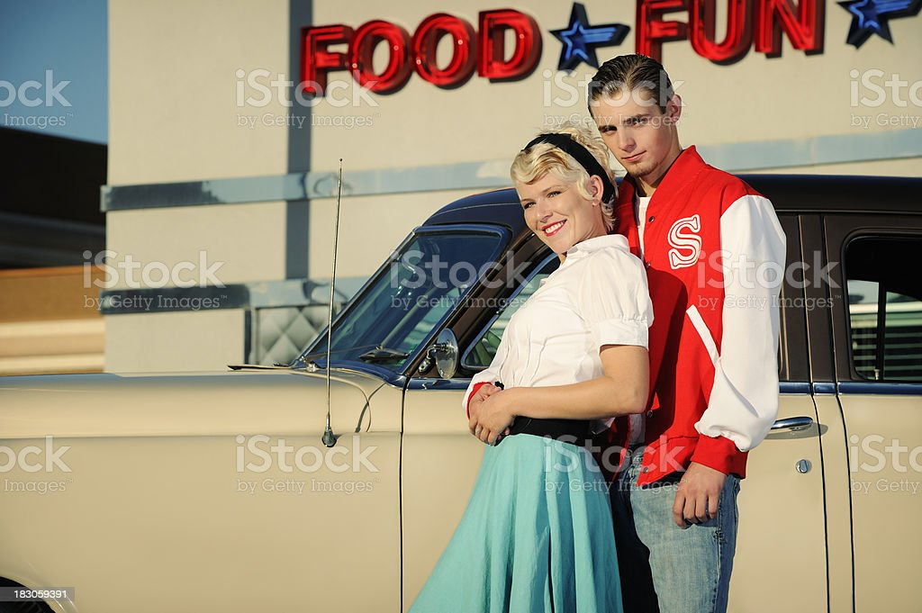 Retro 50's Couple Standing Near Old Car And Diner royalty-free stock photo