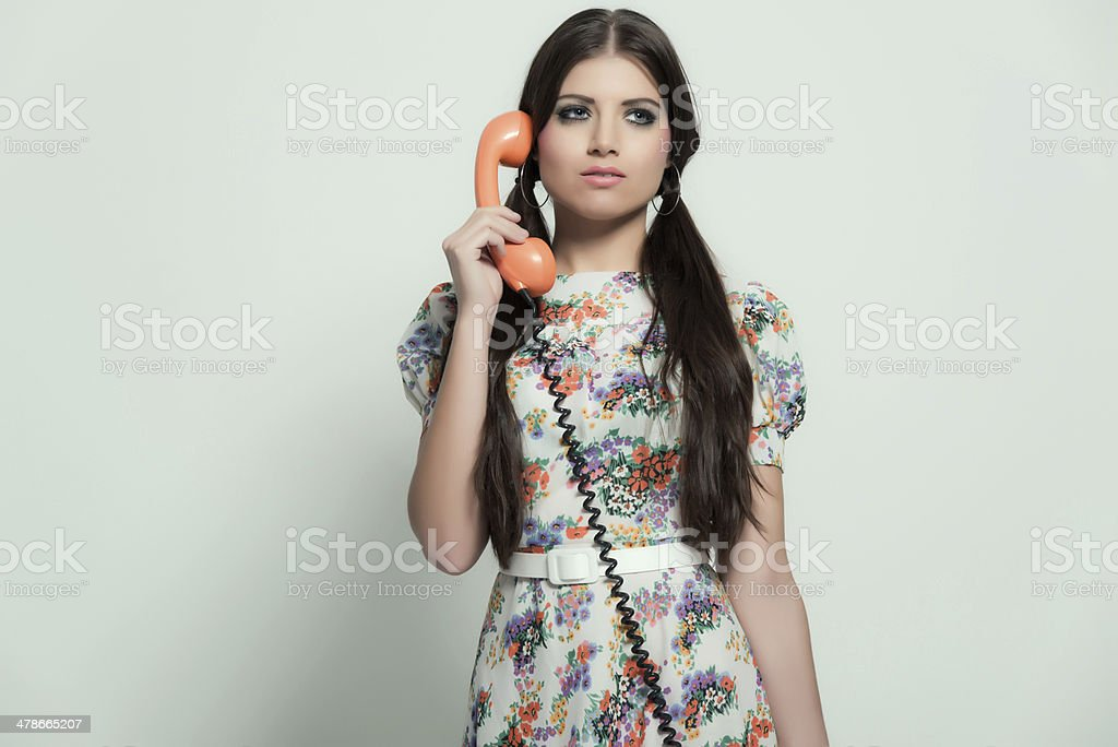 Retro 70s fashion. Pretty brunette girl with long hair. Calling. stock photo
