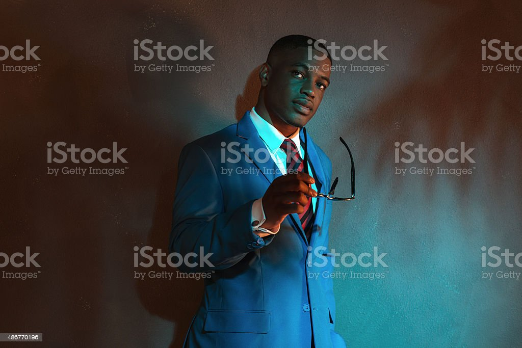 Retro african american businessman in blue suit holding sunglasses. stock photo