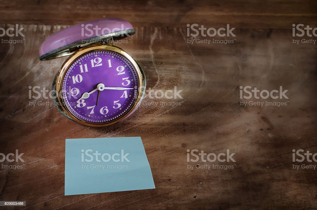 Retro alarm clock and blue sticky note stock photo