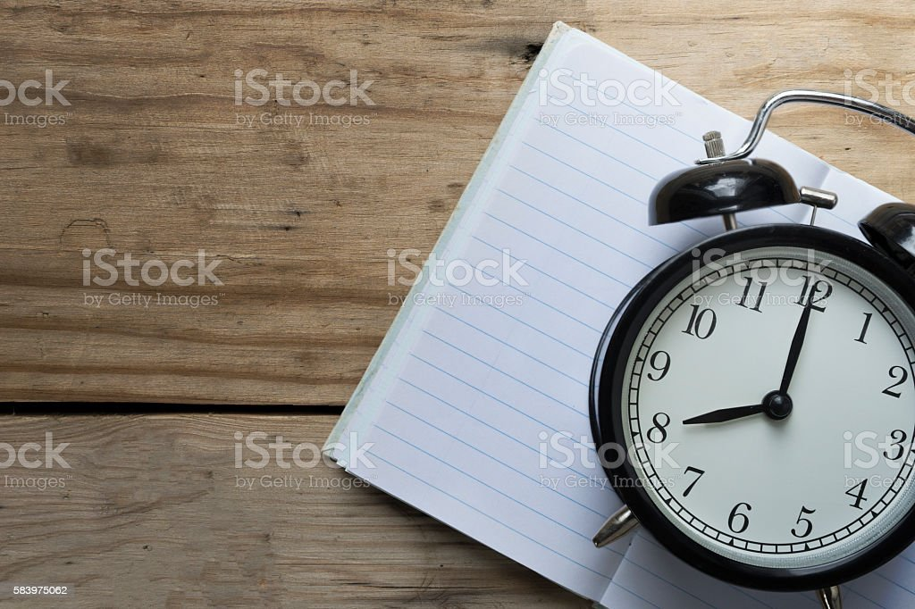 Retro alarm clock and book on wooden table stock photo