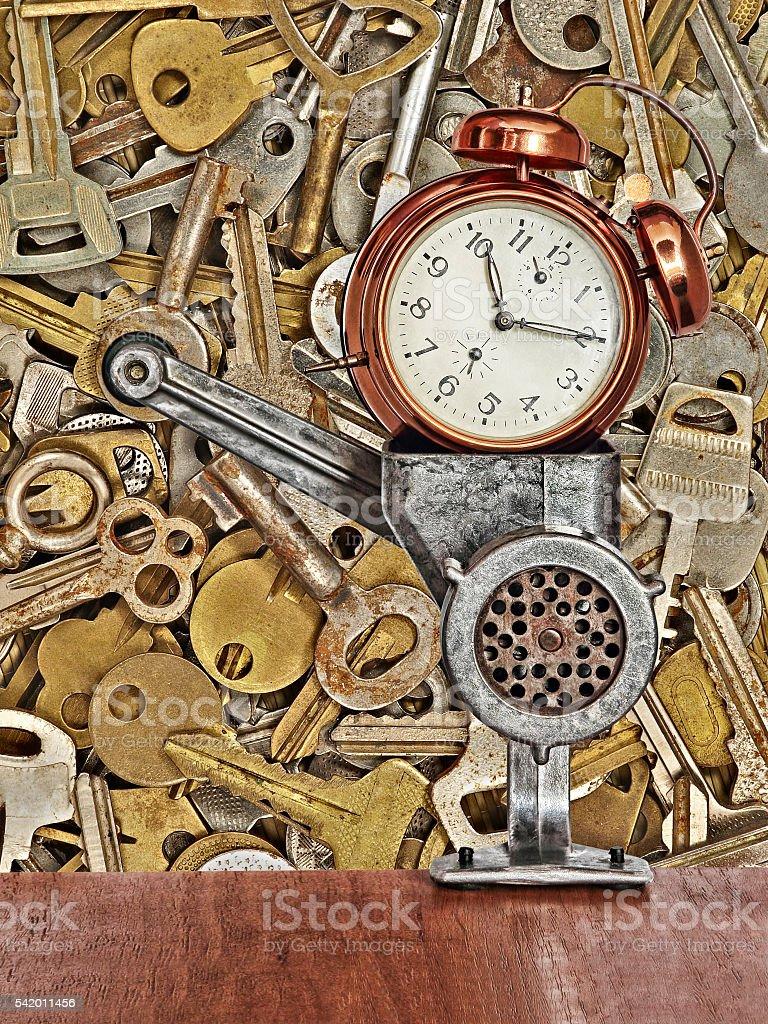 Retro alarm clock in meat grinder on metal keys background. stock photo