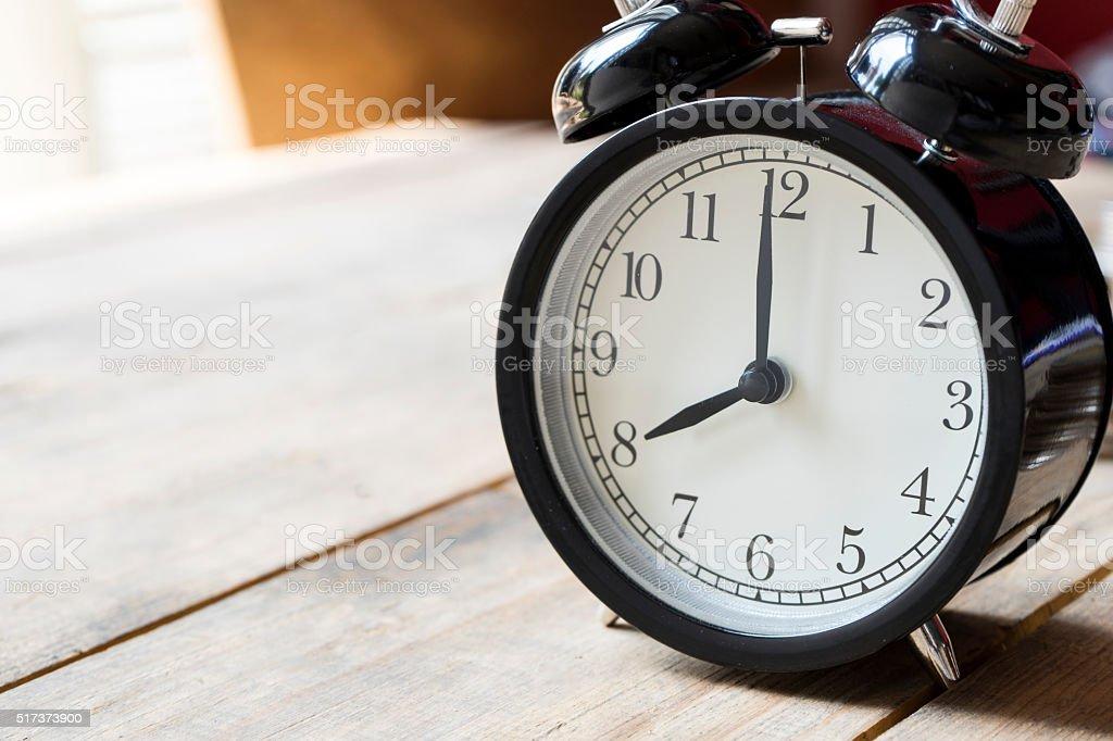 Retro alarm clock on wooden table stock photo