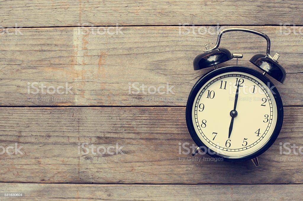 Retro alarm clock on wooden table, vintage style stock photo