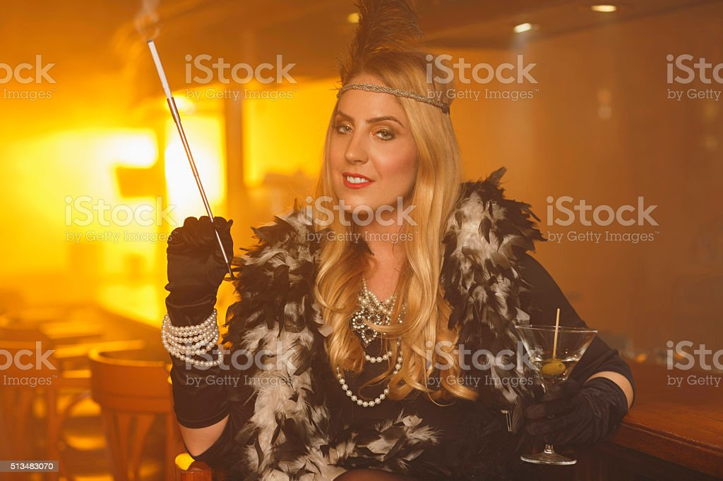 Retro bar  Old-fashioned  young woman drinking martini  Smoking cigarette stock photo