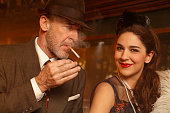 Retro bar  Senior man lighting a cigarette and young woman