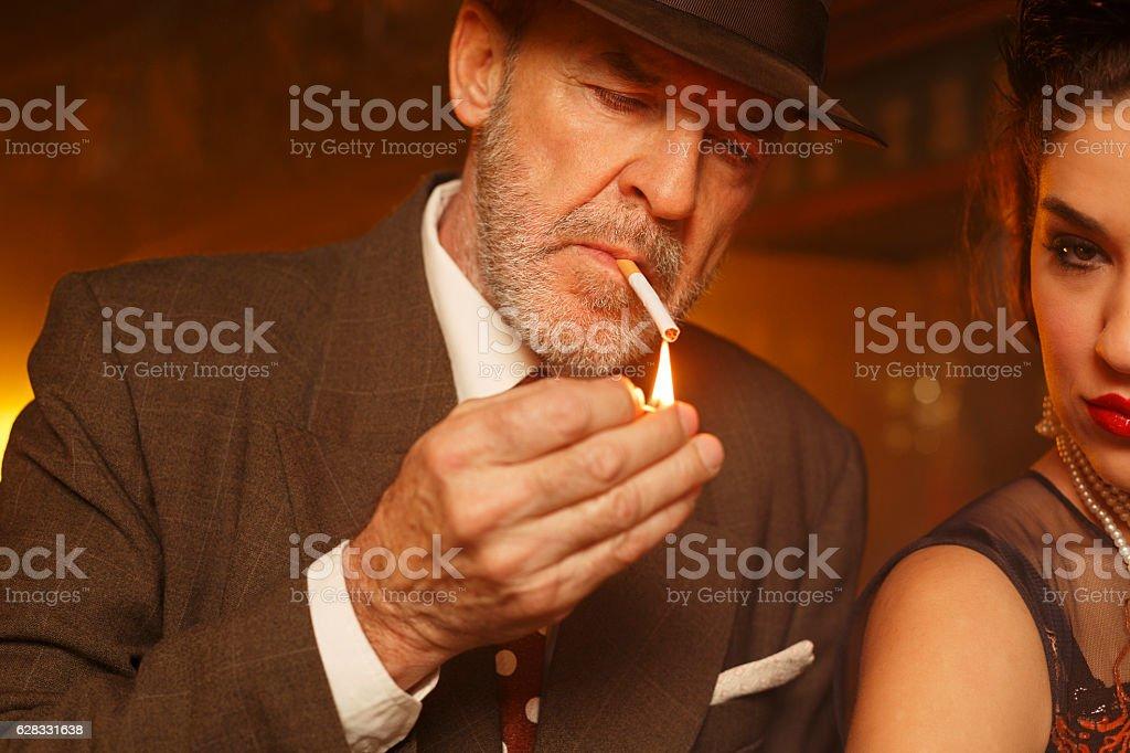 Retro bar  Senior man lighting a cigarette and young woman stock photo