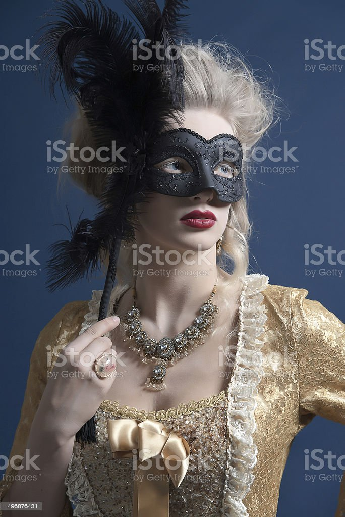 Retro baroque fashion woman wearing gold dress. Holding black mask. royalty-free stock photo