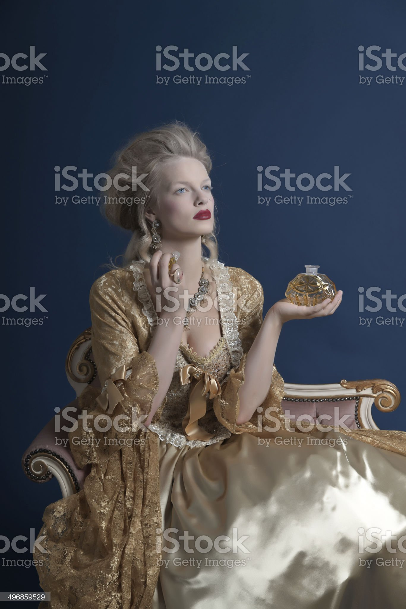 Retro baroque fashion woman wearing gold dress. Holding perfume bottle. royalty-free stock photo