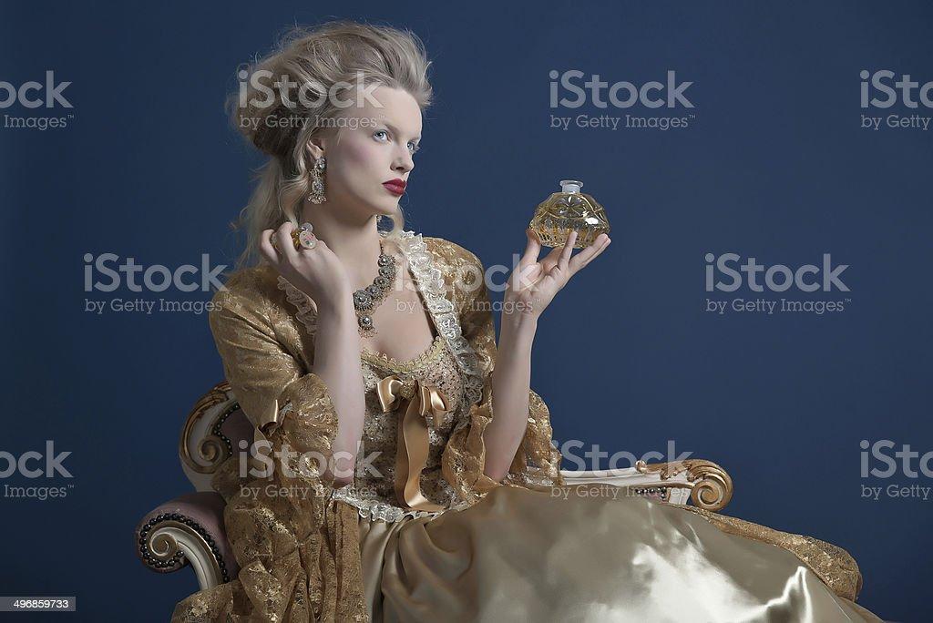 Retro baroque fashion woman wearing gold dress. Holding perfume bottle. royalty-free stock photo