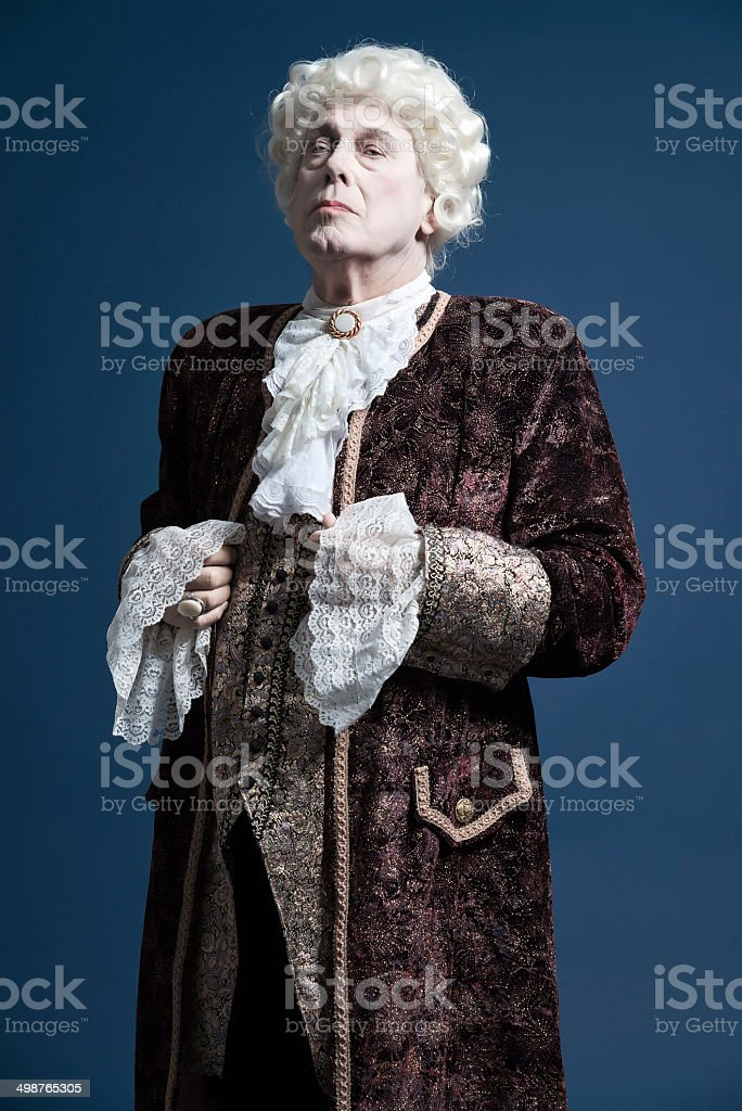 Retro baroque man with white wig standing and looking arrogant. stock photo