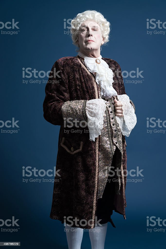 Retro baroque man with white wig standing and looking arrogant. royalty-free stock photo