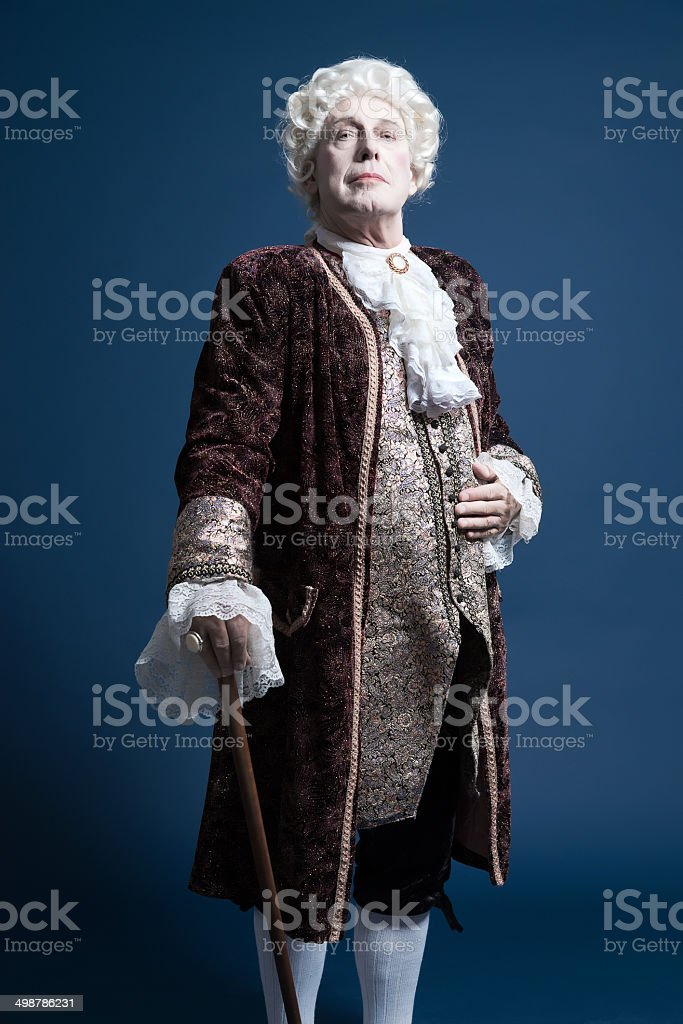 Retro baroque man with white wig standing with walking stick. stock photo