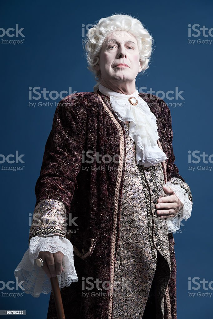 Retro baroque man with white wig standing with walking stick. royalty-free stock photo