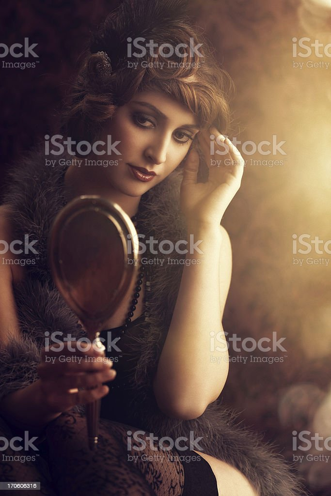 retro beauty lookin at herself in a silver hand mirror stock photo