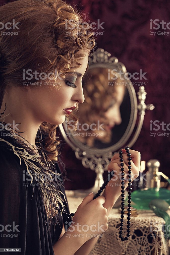retro beauty looking at a necklace royalty-free stock photo