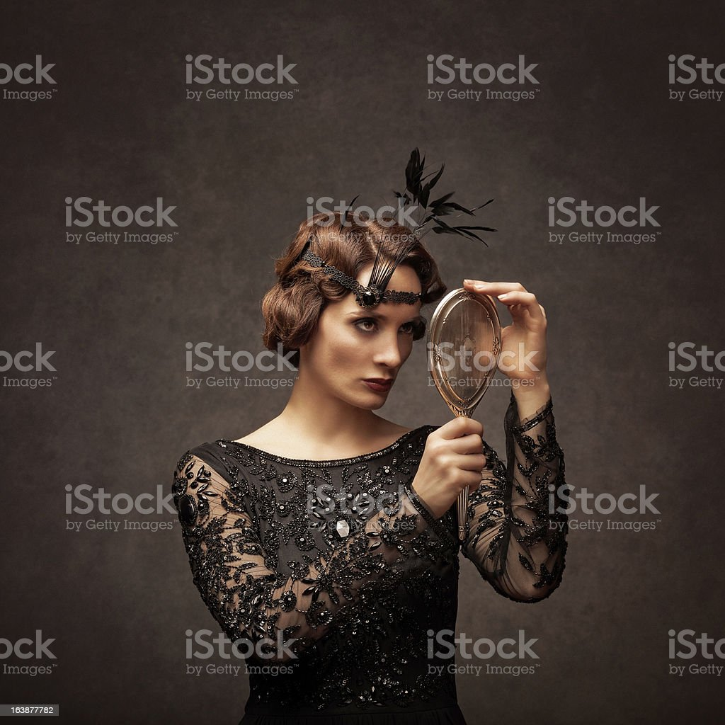retro beauty looking at herself in a silver hand mirror royalty-free stock photo