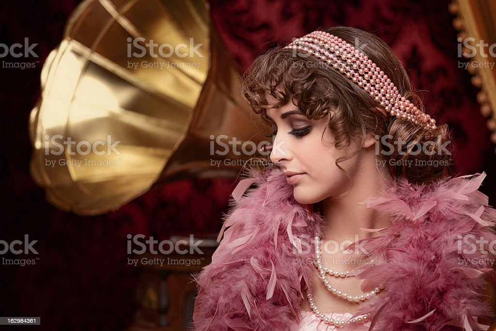 retro beuty with feather boa listening music in boudoir stock photo