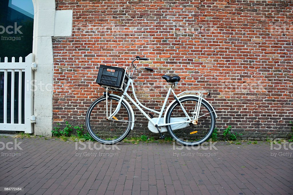 Retro bicycle on roadside with vintage brick wall background stock photo