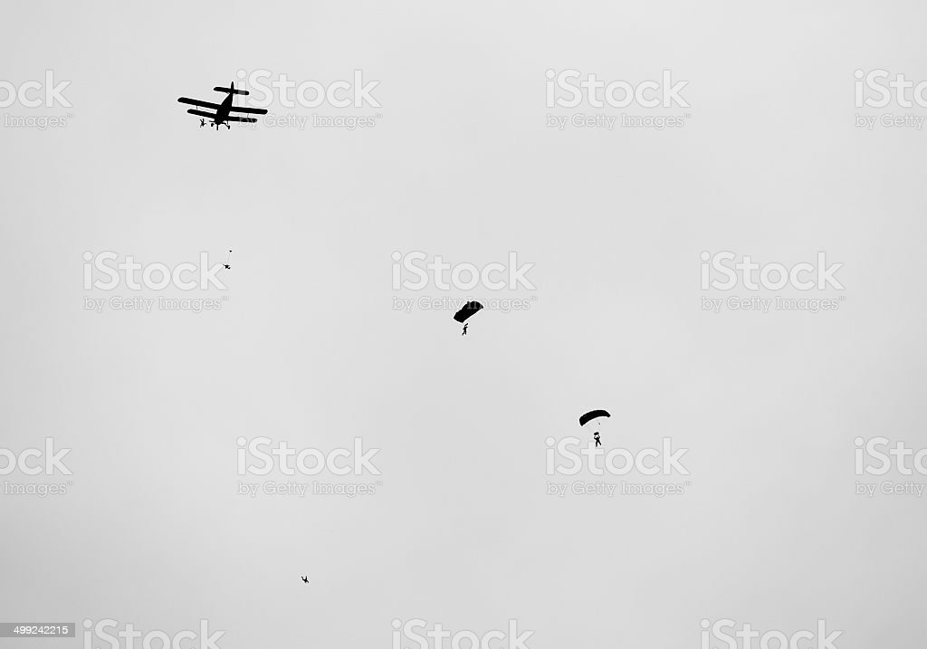 retro  biplane with skydivers in black and white stock photo