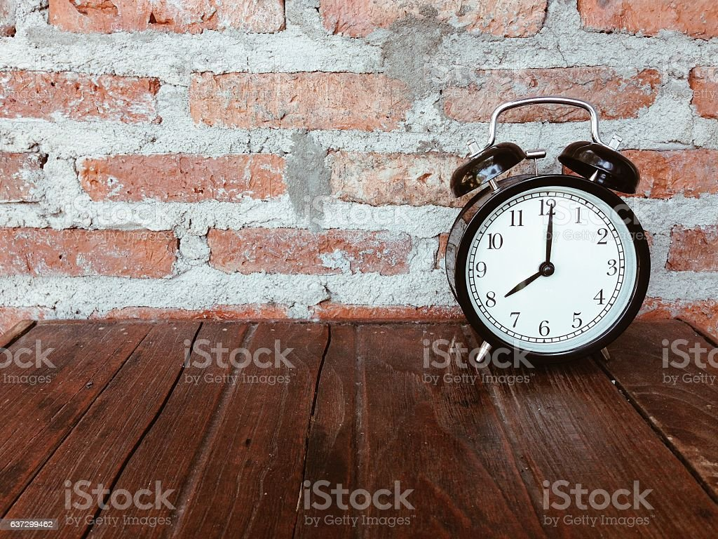 Retro black alarm clock on wooden table stock photo