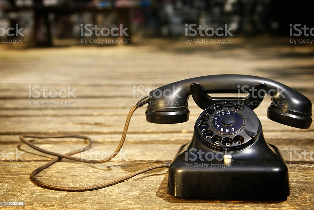 Retro black Bakelite phone with woven cord on wood surface stock photo