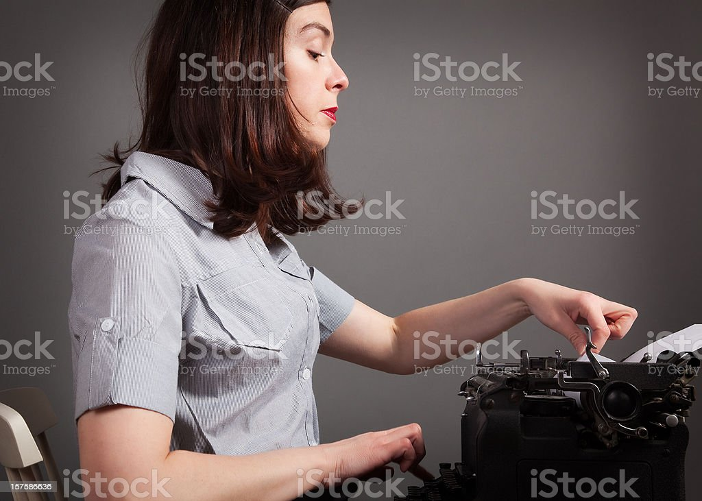 Retro brown-haired working girl feeds paper into old-style black typewriter royalty-free stock photo