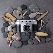 Retro camera with seashells on stone background. Top view
