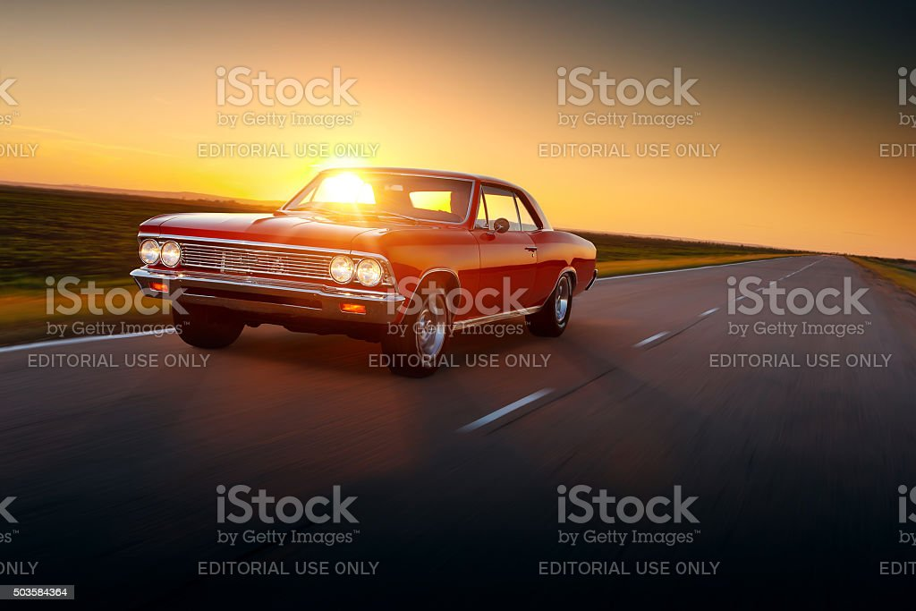 Retro car Chevrolet Malibu 1960s drive speed on road sunset stock photo