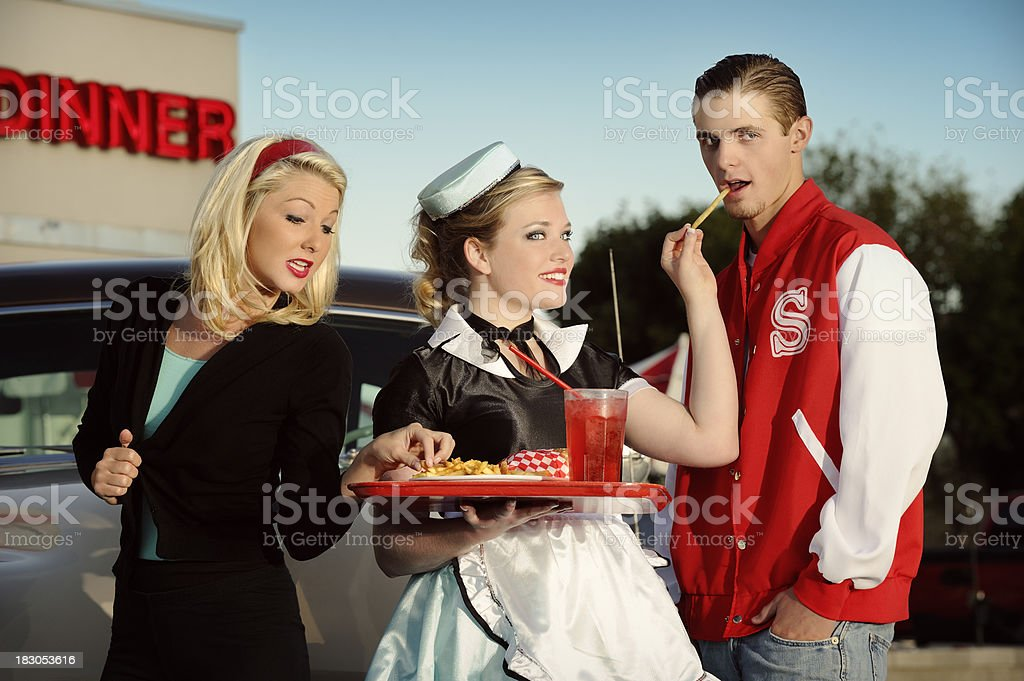 Retro Car Hop At Diner Bringing Food Tray To Customers stock photo