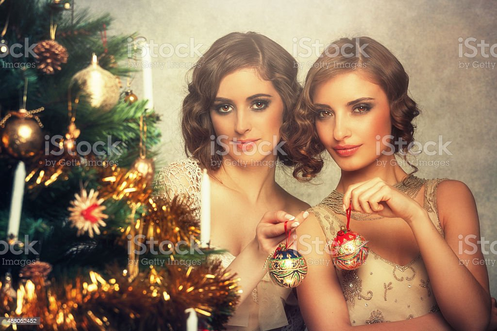 retro christmas - girls decorating a christmas tree stock photo