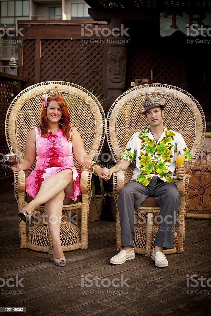 Retro couple in tiki bar stock photo